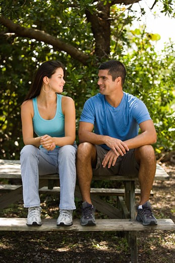 Stock Photo: 1663R-41930 Mid adult man and a young woman looking at each other