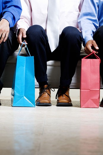 Low section view of three people sitting on a couch holding shopping bags : Stock Photo