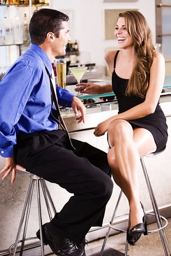 Side profile of a mid adult man and a young woman at a bar counter : Stock Photo