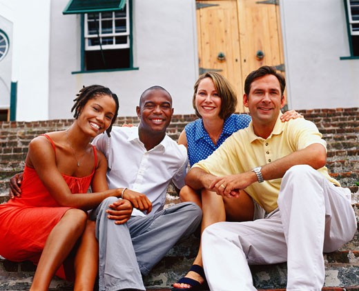 Portrait of two young couples sitting on steps and smiling, Bermuda : Stock Photo