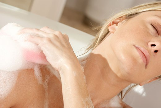 Close-up of a young woman scrubbing her shoulder with a bath sponge : Stock Photo