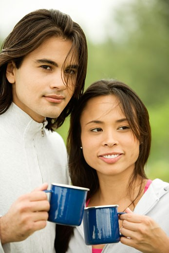 Close-up of a young couple holding coffee cups : Stock Photo