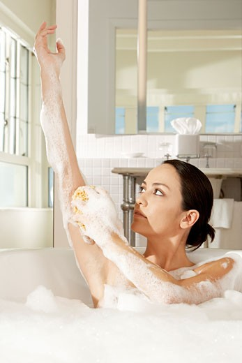 Stock Photo: 1663R-42673 Young woman using a bath sponge on her arm