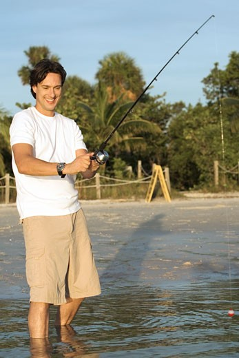Mid adult man holding a fishing rod : Stock Photo