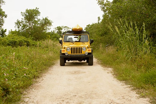 Jeep on a dirt road with a kayak on its roof : Stock Photo