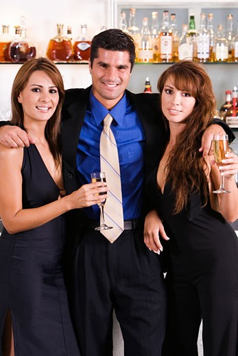 Stock Photo: 1663R-43227 Portrait of a mid adult man with his arms over two young women