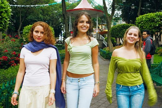 Stock Photo: 1663R-4359 Three young women walking on a walkway in a park