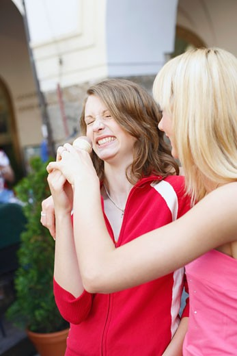 Close-up of a teenage girl holding an ice-cream in front of another woman : Stock Photo