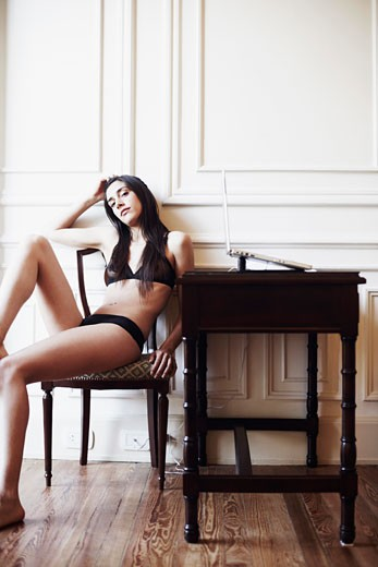 Portrait of a young woman in lingerie sitting on a chair with a laptop on a table beside her : Stock Photo