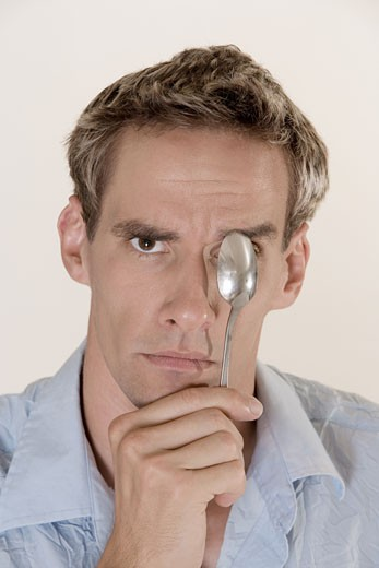 Portrait of a young man covering his eye with a spoon : Stock Photo