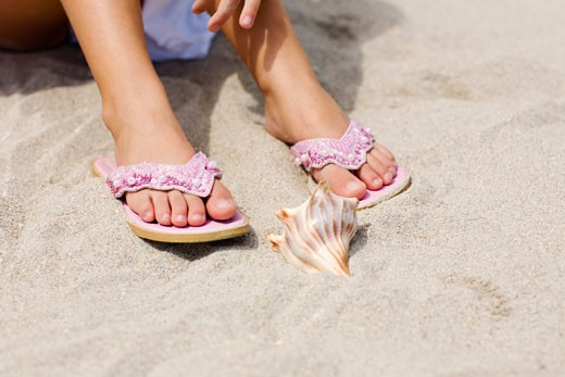 Low section view of a girl on the beach with a conch shell in front of her : Stock Photo