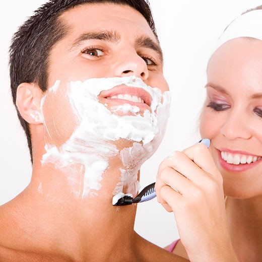Stock Photo: 1663R-44521 Close-up of a young woman shaving a mid adult man's face