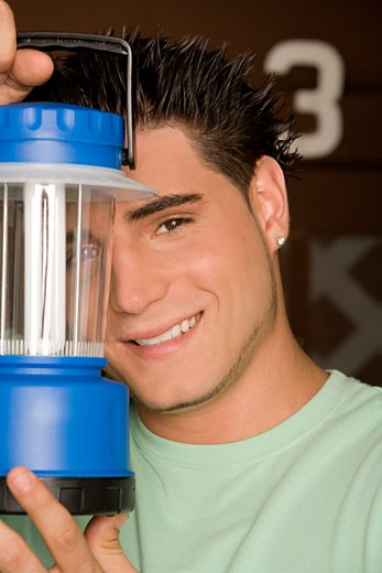 Stock Photo: 1663R-44614 Portrait of a young man holding a lantern