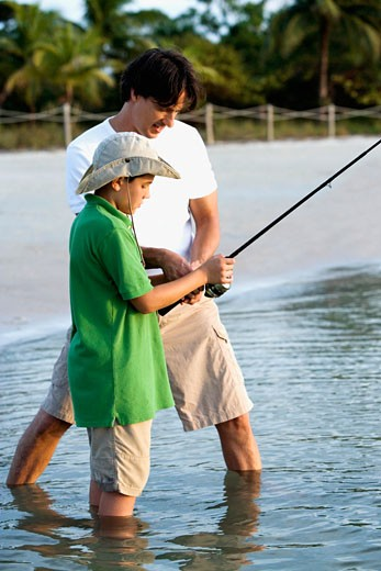 Side profile of a father and his son fishing : Stock Photo