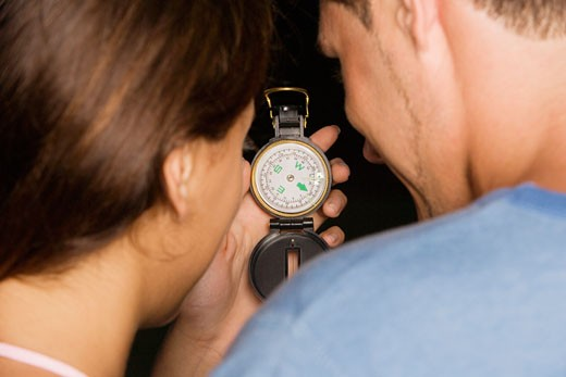 Rear view of a young man and a teenage girl holding an antique compass : Stock Photo