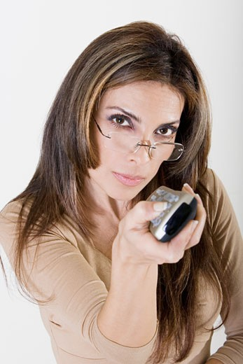 Portrait of a young woman using a remote control : Stock Photo