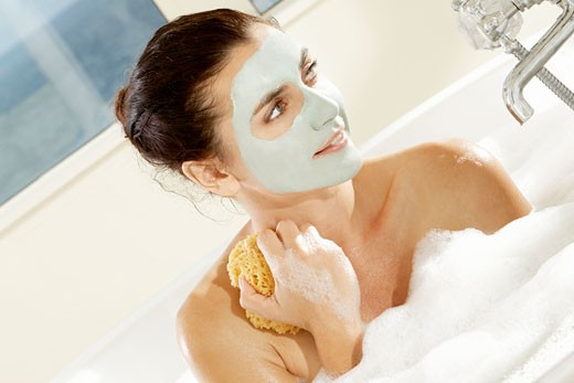Stock Photo: 1663R-45100 Close-up of a young woman with a facial mask holding a bath sponge