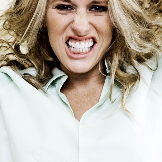 Portrait of a young woman clenching her teeth : Stock Photo
