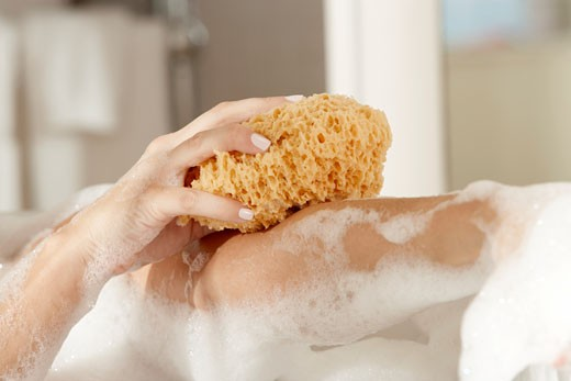 Stock Photo: 1663R-45358 Close-up of a young woman's hands scrubbing her body with a bath sponge