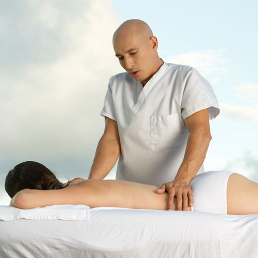 Young woman getting a back massage : Stock Photo