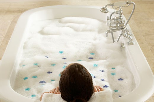 High angle view of a woman in a bubble bath with flower petals : Stock Photo