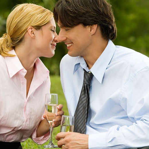 Close-up of a businessman and a businesswoman sitting in the park holding champagne flutes : Stock Photo