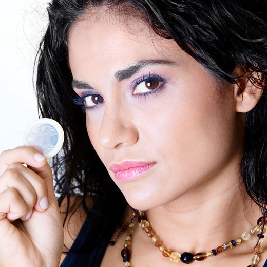 Portrait of a young woman holding a condom : Stock Photo