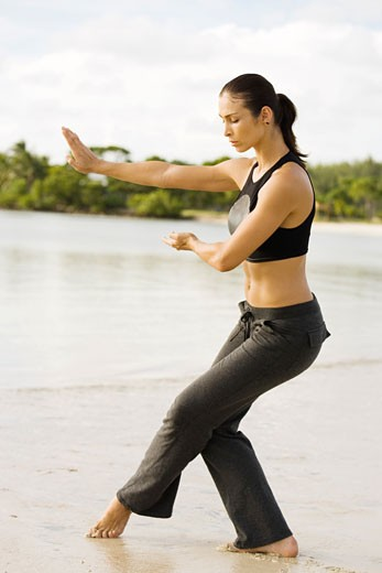 Stock Photo: 1663R-45681 Side profile of a young woman practicing martial arts on the beach