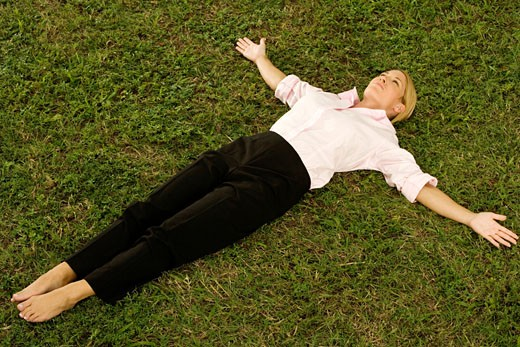 Young woman lying on the grass : Stock Photo