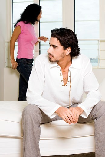 Close-up of a young man sitting with a young woman standing behind him : Stock Photo