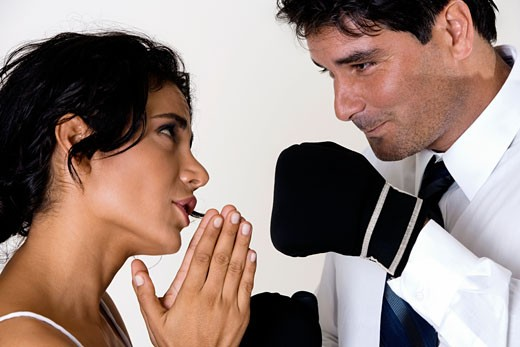 Side profile of a young woman pleading before a mid adult man wearing boxing gloves : Stock Photo