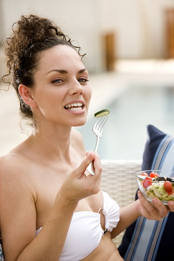 Portrait of a young woman eating fruit salad : Stock Photo