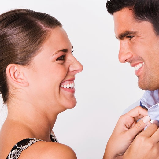 Side profile of a young woman buttoning the shirt of a mid adult man : Stock Photo