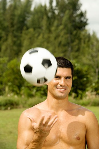 Stock Photo: 1663R-46833 Portrait of a mid adult man tossing a soccer ball