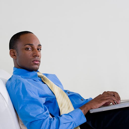 Side profile of a businessman using a laptop : Stock Photo