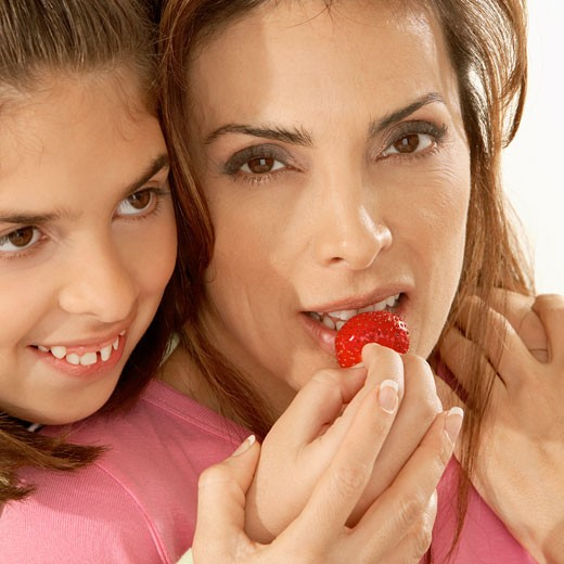 Close-up of a daughter feeding her mother a strawberry : Stock Photo