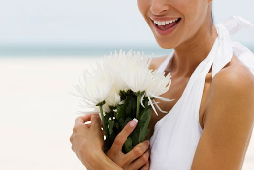 Close-up of a young woman holding flowers on the beach : Stock Photo