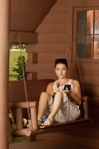 Portrait of a young woman sitting on a swing and holding a makeup brush : Stock Photo