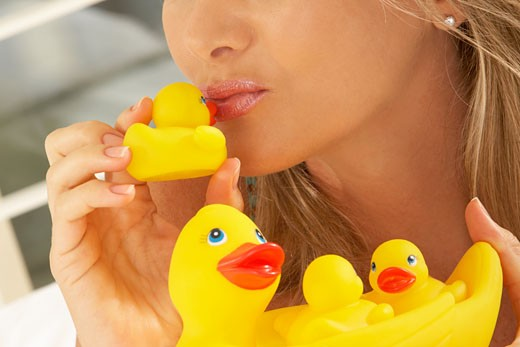 Close-up of a mid adult woman kissing a rubber duck : Stock Photo