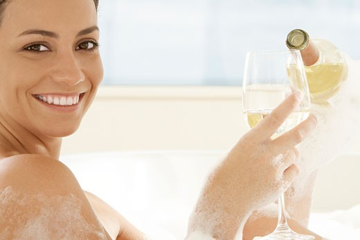 Stock Photo: 1663R-47568 Portrait of a young woman pouring white wine into a wineglass