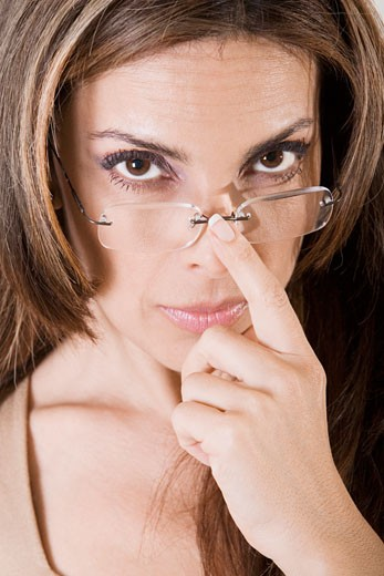 Portrait of a young woman adjusting her eyeglasses : Stock Photo