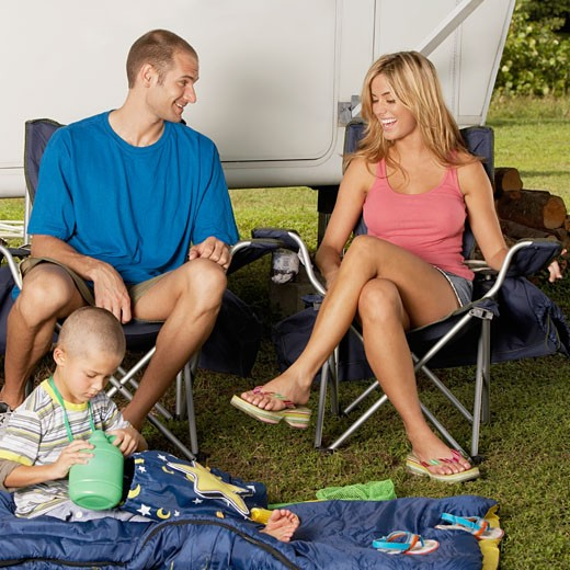 Stock Photo: 1663R-47627 Boy sitting on a quilt with his parents looking cheerful