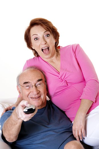 Portrait of a senior couple watching television : Stock Photo