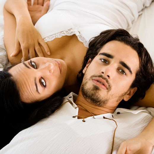 Portrait of a young couple lying on the bed : Stock Photo