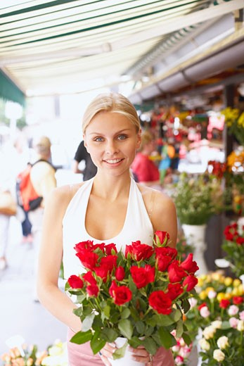 Stock Photo: 1663R-4788 Portrait of a young woman holding a bouquet of flowers in a flower shop