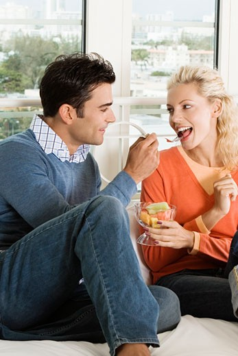 Close-up of a young man feeding salad to a young woman : Stock Photo