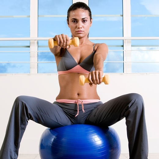 Portrait of a young woman exercising with dumbbells on a fitness ball : Stock Photo