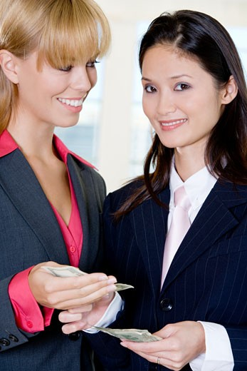 Portrait of a businesswoman giving a dollar bill to another businesswoman : Stock Photo