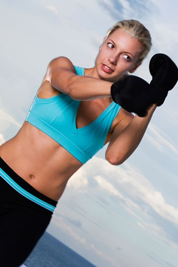 Stock Photo: 1663R-48280 Low angle view of a young woman wearing boxing gloves
