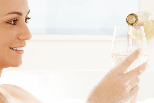 Close-up of a young woman pouring white wine into a wineglass : Stock Photo